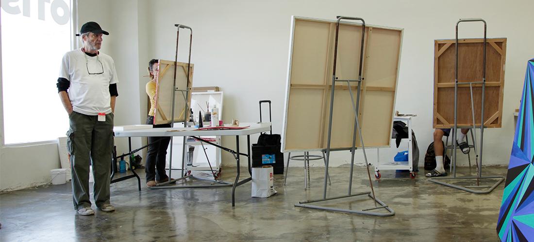 Otis faculty member Michael Schrier overlooks students painting