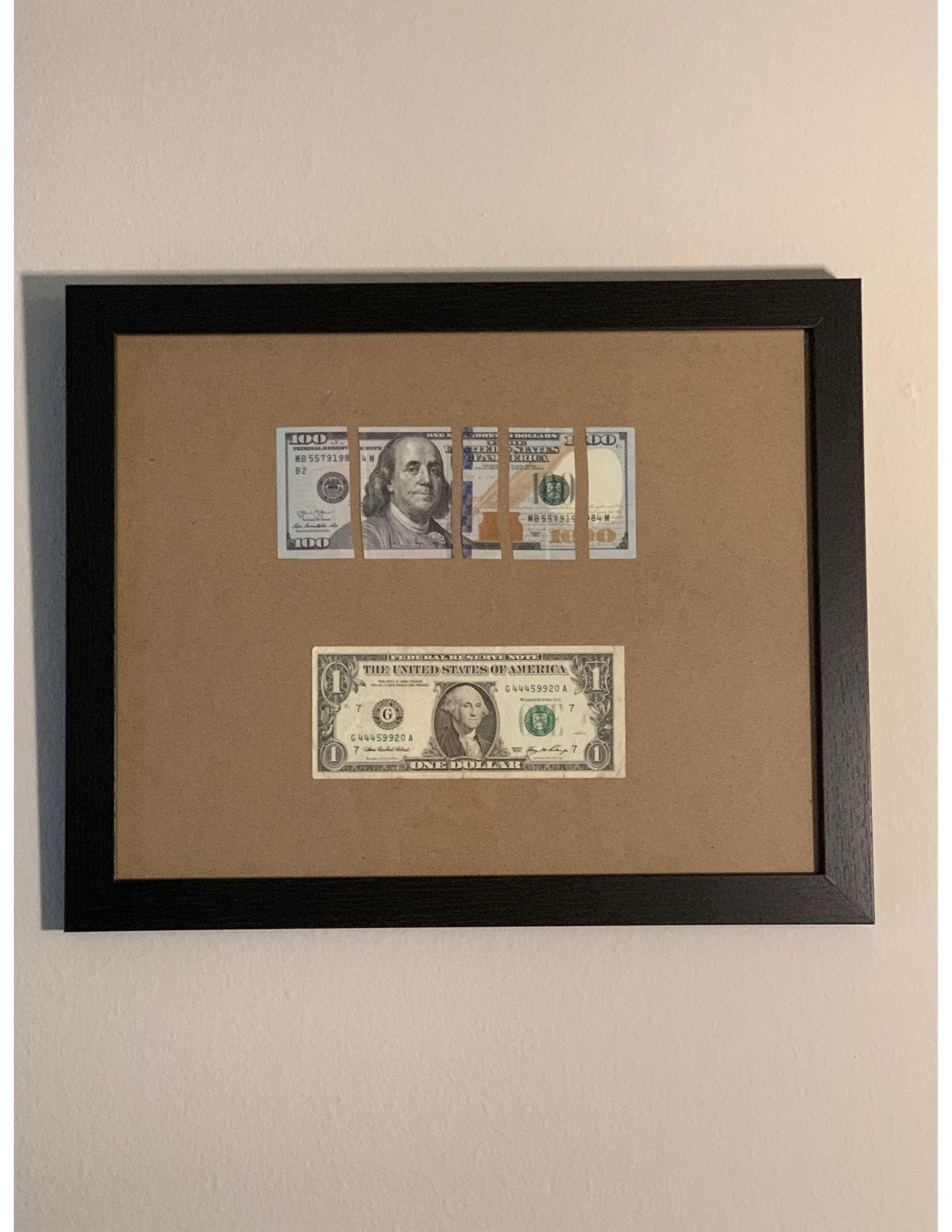 Dollar bills cut and mounted in frame
