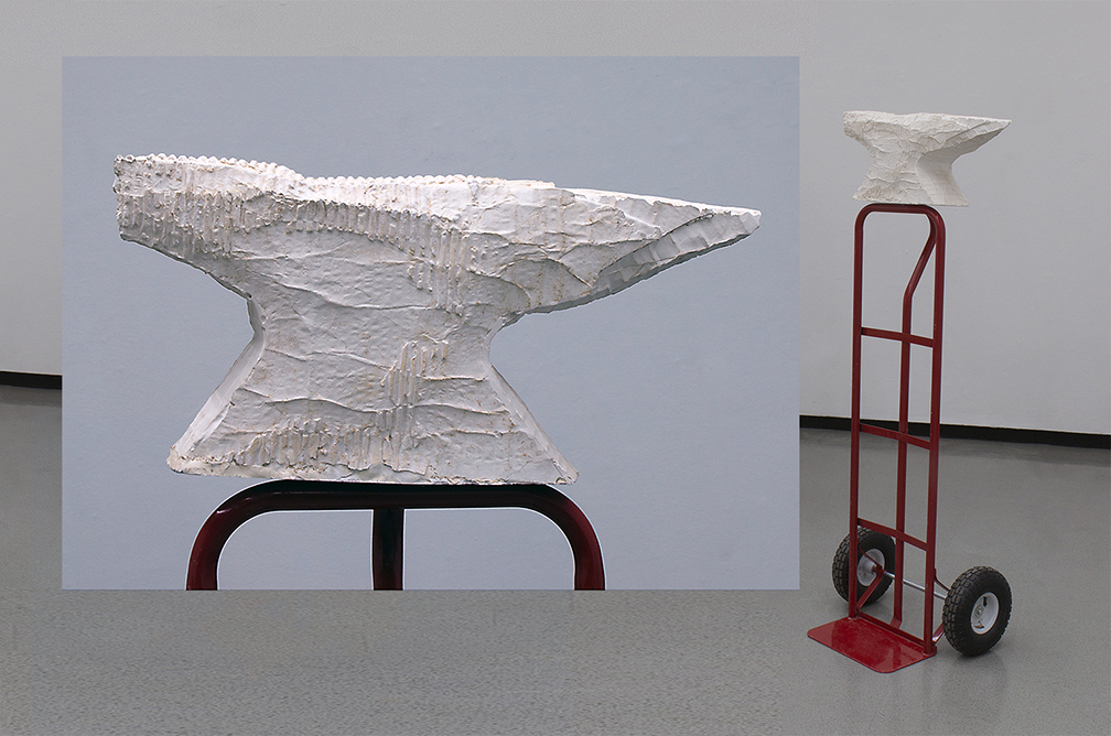Mixed media in anvil form and mounted atop red moving dolly.