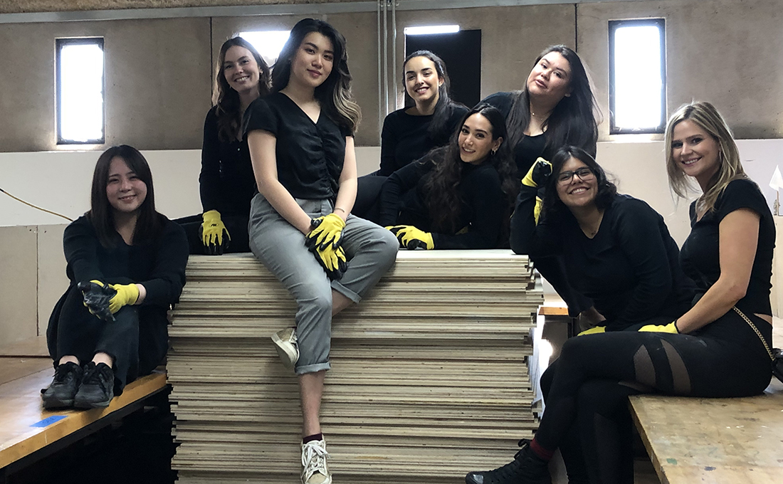 Proud and exhausted seniors posing on 109 sheets of plywood