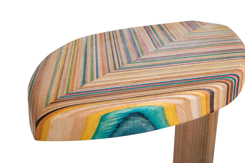 dynamically shaped side tables that feature multicolored striped wood tops that are constructed out of the recycled wood from three skateboards