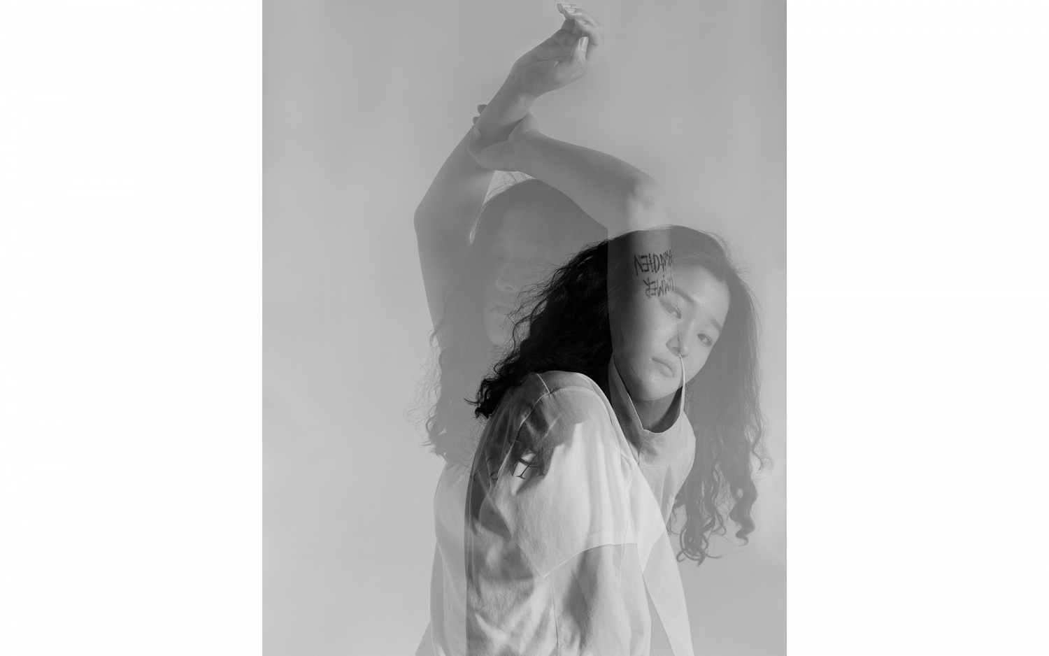 Black and white, double-exposed photo of young woman.