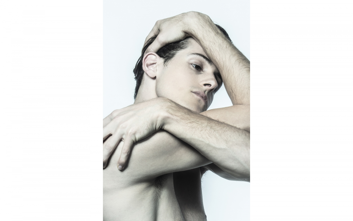 Color photo of young man holding his head in his arms.