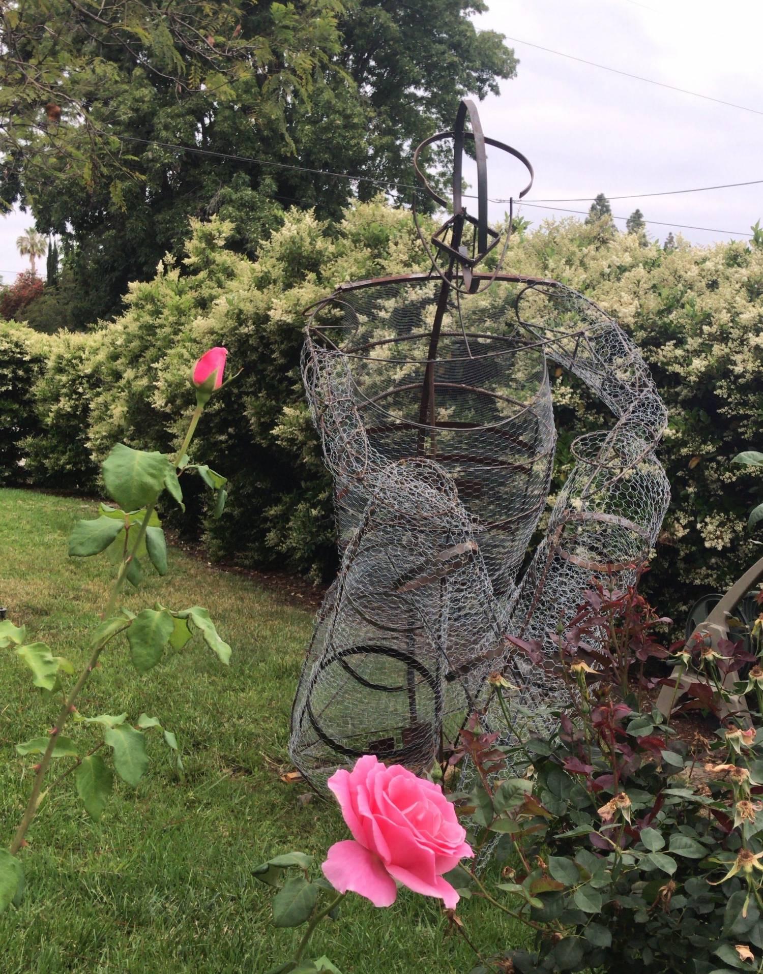 Welded figure sculpture installed on grass yard/garden.