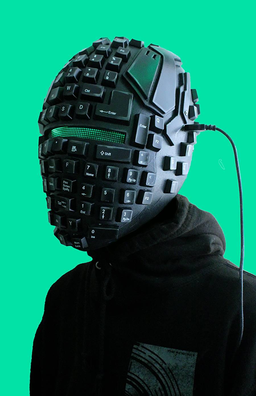 Black plastic helmet made of green LED lights, keyboard keys, scrap computer parts, and laptop charger.