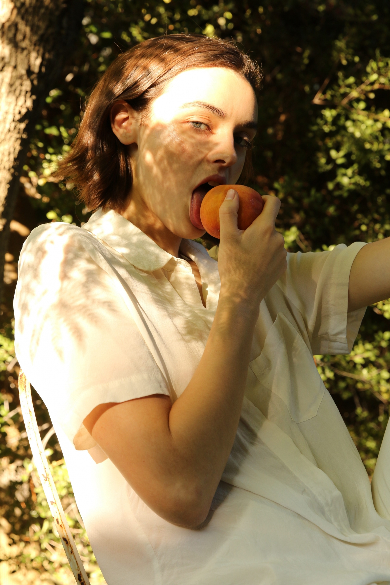Woman licking a peach while gazing into the camera.