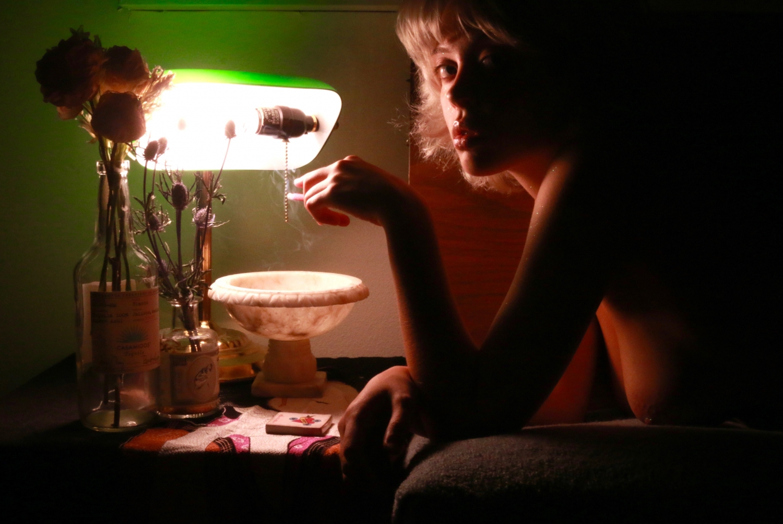 Woman lying down smoking a cigarette gazing into the camera.