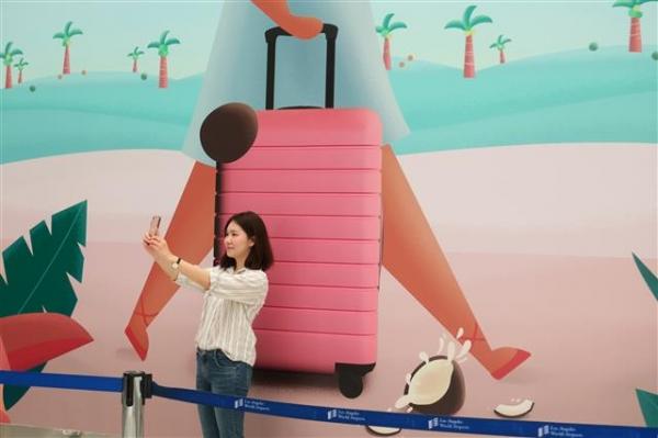 "2018 Otis College Graduate Alice Hur takes a selfie in front of her design, ""Paradise."""