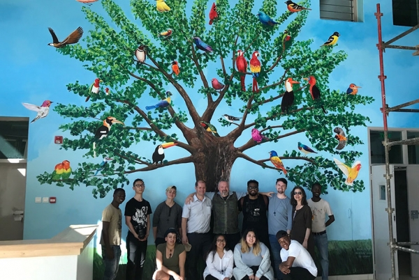 Otis group in front of a mural by Jacaranda students depicting a tree full of colorful birds