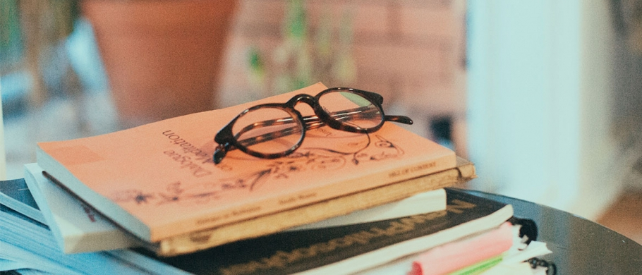 photos of books stacked up with reading glasses on top