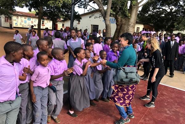 Students at the Jacaranda School greet the Otis group.