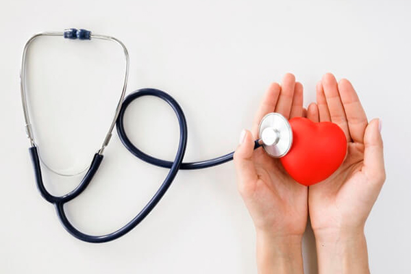 Stethoscope with heart in hands