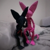 Please Don't Cry Brain Cats, by Cactus Springman. A photographic print of two soft sculptures, a black cat and pink cat. The black cat is sitting on a pillow, head in their hands, while the pink cat tries to comfort them. Both cats are on top of a human-sized bed.