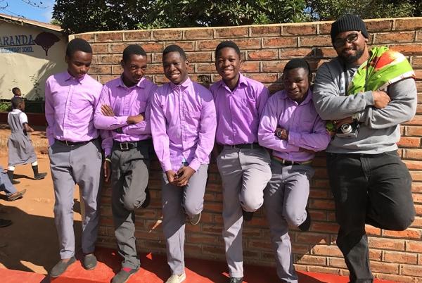 Students pose on a wall outside the Jacaranda School.